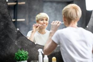 Donna si lava i denti allo specchio